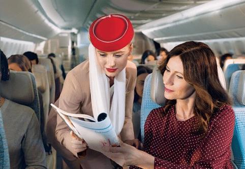 Emirates stewardess helping passenger